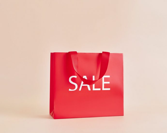 red paper bag with sale sign